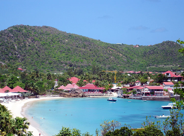Beach goers frolick in the water of St. Barth's
