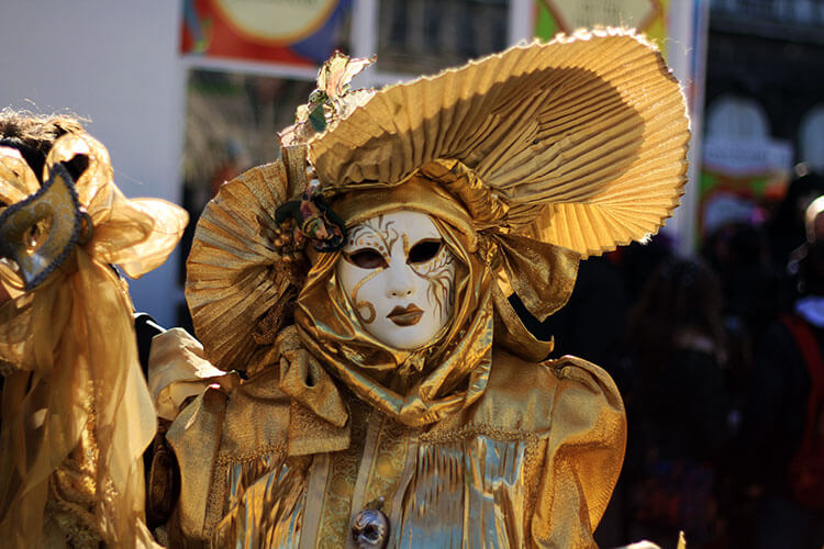 A person dressed up in a gold costume with a gold and white mask completely covering the face