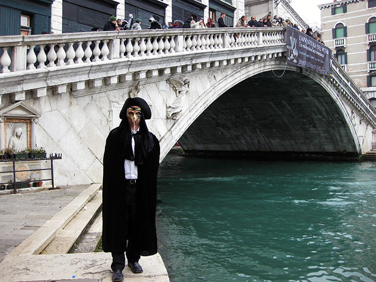 Tim dressed as the plague doctor and posing in front of the Rialto Bridge