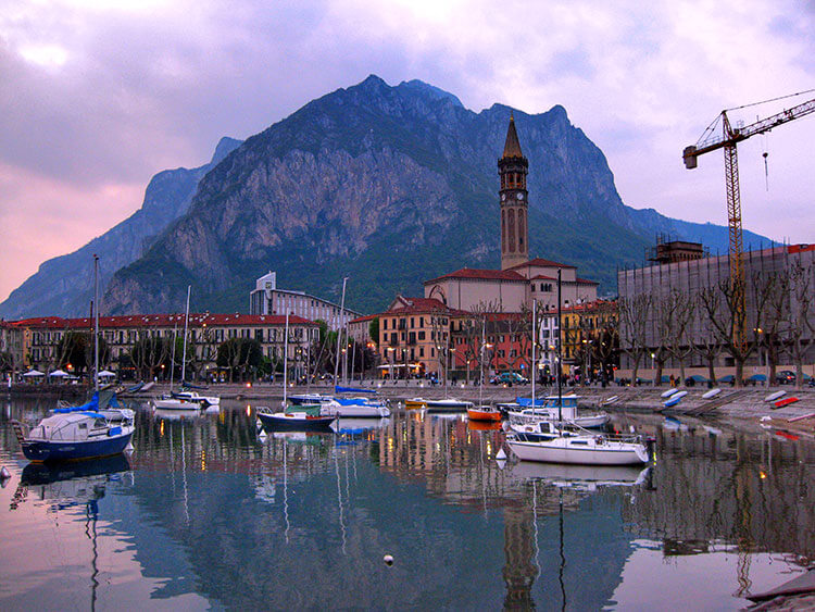 The bell tower stands with a mountain as a backdrop and the boats reflecting on the water in the harbor in Lecco