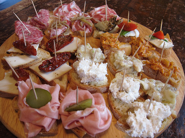 Various cicchetti on a round wooden try