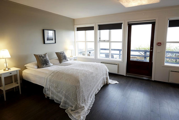 A balcony sea view room with dark wood floor and white linens