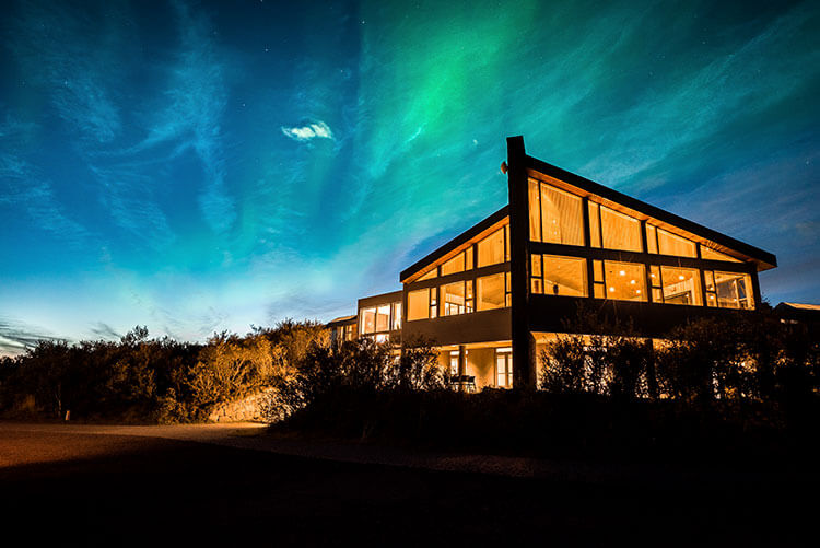 Northen Lights light up the sky behind the glass Hotel Husafell
