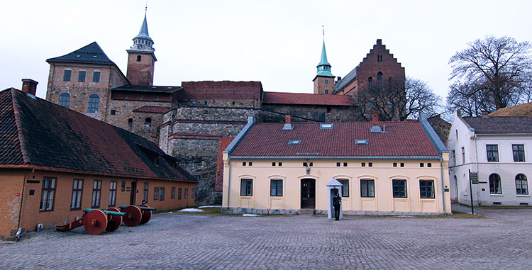 A guard stands at the entrance as the medieval Akershus Slott rises up behind him