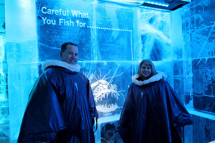 Tim and Jennifer in the Arctic capes provided to keep you warm at Magic Ice Bar Oslo in front of a giant block of ice with a scary fish with razor sharp teeth etched in to it