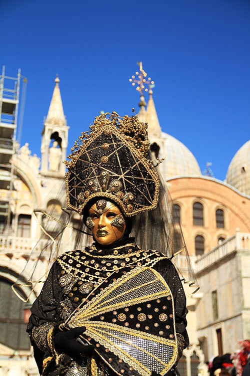 A carnival goer dressed up in black and gold with a full face mask
