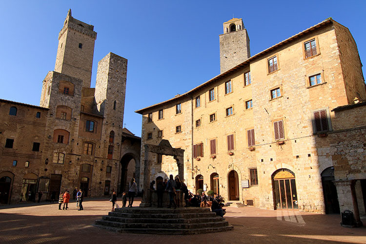 The medieval towers cast shadows on the Piazza della Cisterna in the center of San Gimignano