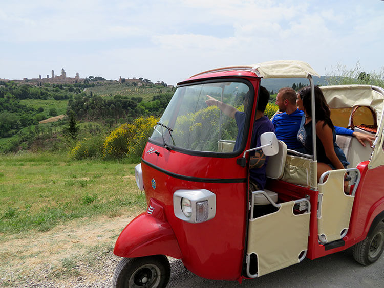 The guide points toward San Gimignano from a roadside viewpoint of the medieval town during the tuk tuk tour of Tuscany
