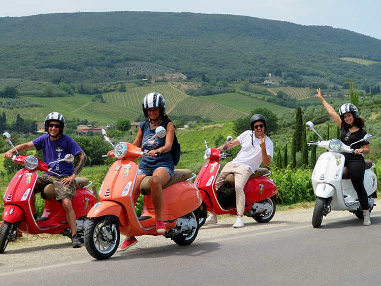 A group of four poses on their red vespas on the Vespa Tour from Florence to San Gimignano with Tuscan countryside in the background