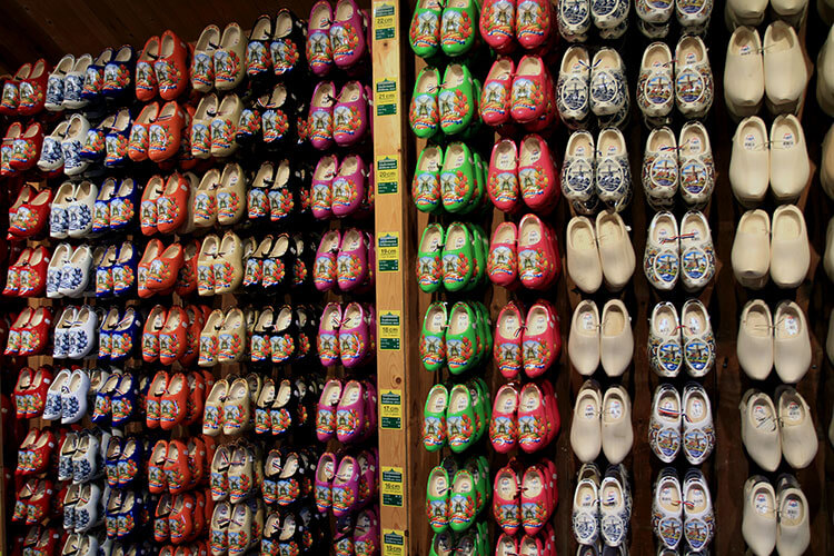 A wall full of women's clogs for sale in a variety of colors, patterns and sizes