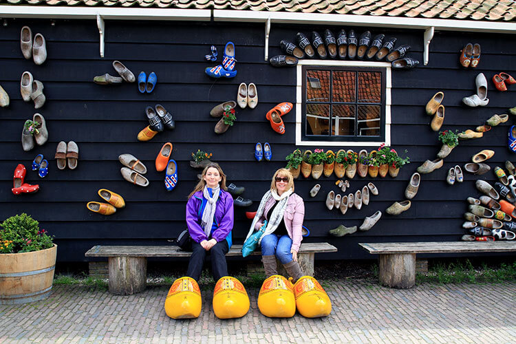 Jennifer and her friend Theresa sitting outside the Clog Workshop in giant yellow clogs