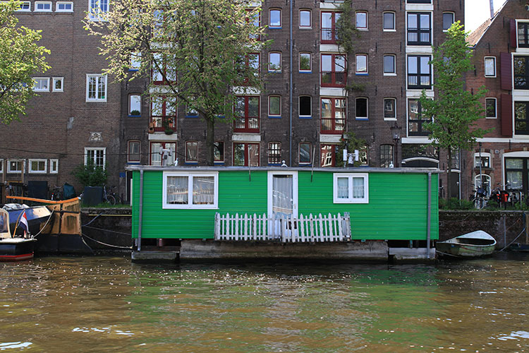 A green houseboat turned in to a permanent house on the Amsterdam canals