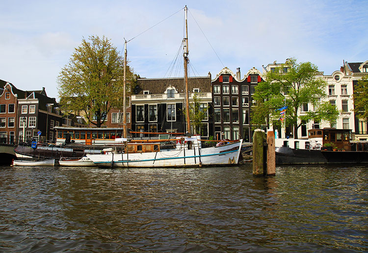 A fishing boat is moored in Amsterdam in front of various tilted houses