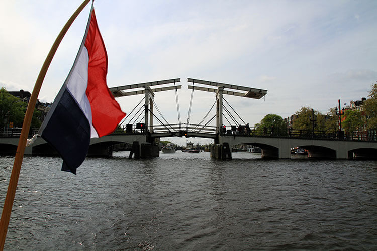 Magere Brug or Skinny Bridge gets ready to raise to let a ship pass through