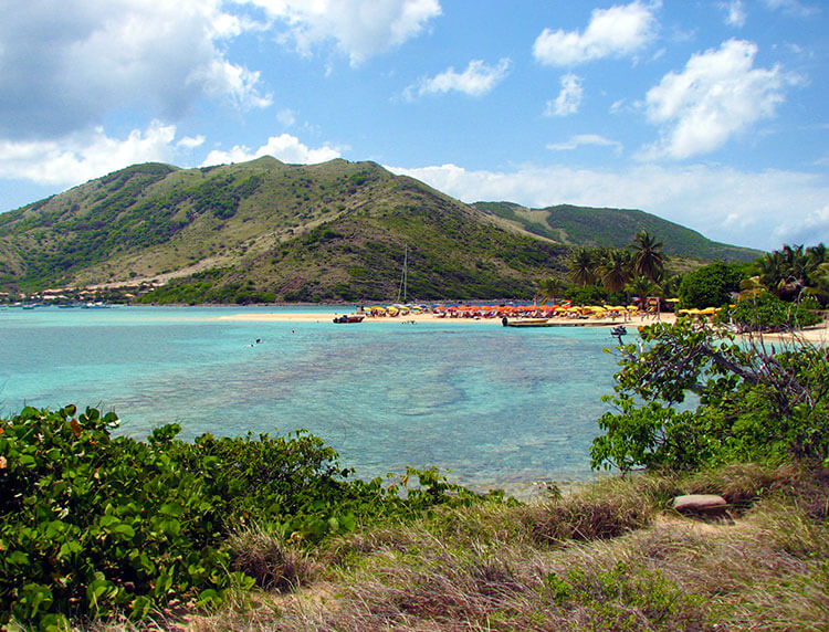 Looking to the spit of sand with umbrellas for rent on Pinel Island from atop a hill on the island in St. Martin