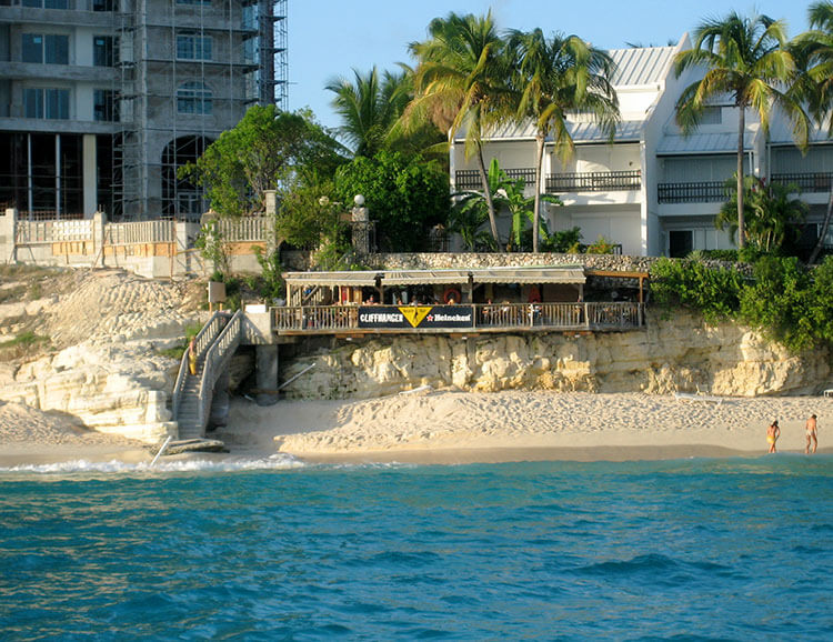 The wooden Cliffhanger Bar is perched overhanging the limestone cliffs just above Cupecoy Beach in St. Maarten