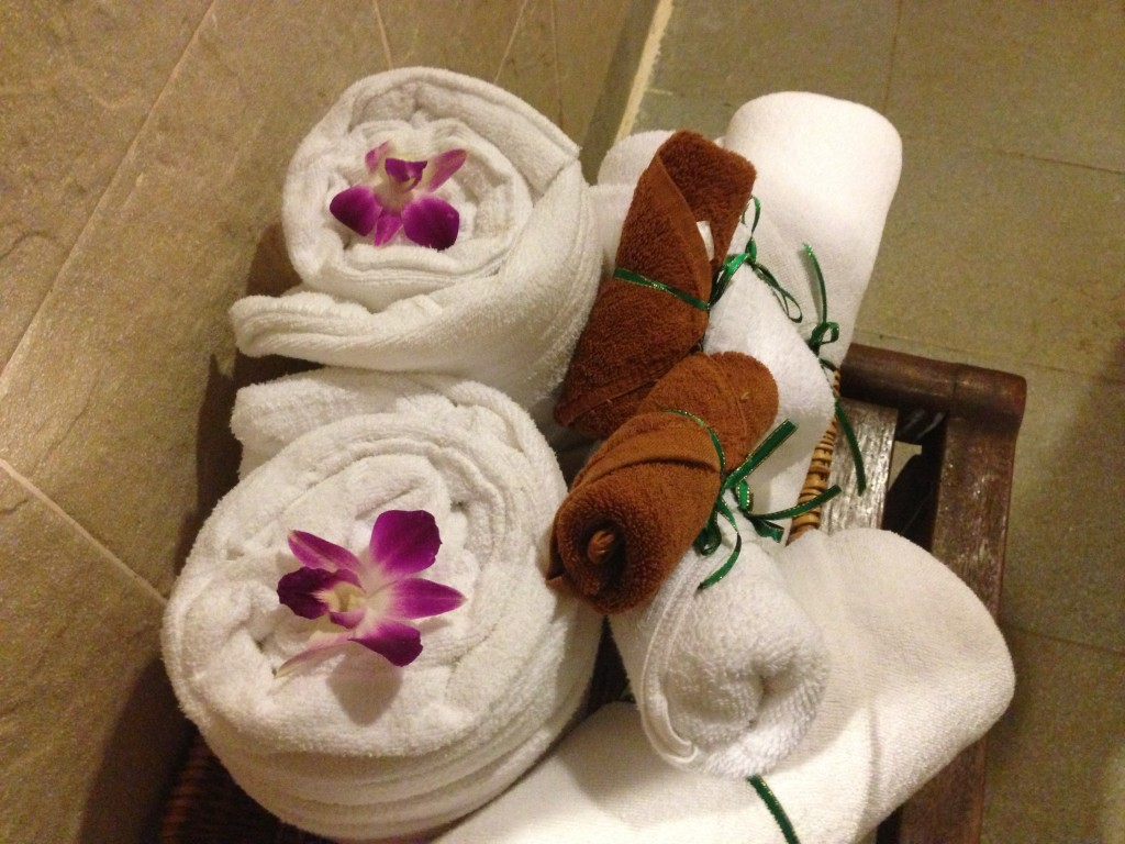 Towels and bathrobes are rolled up and decorated with orchids