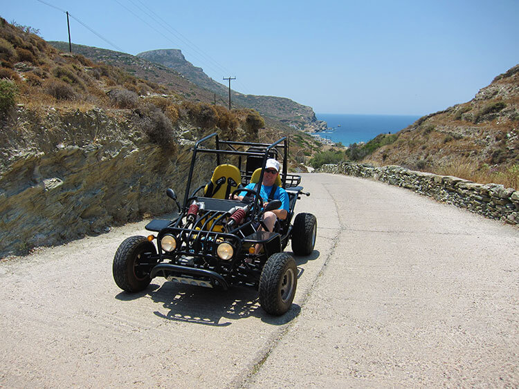 Tim driving our buggy on a road leading down to a beach on Folegandros
