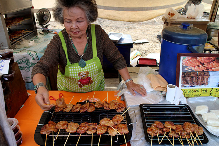 A Thai woman barbecues pork skewers at the Taling Chan market