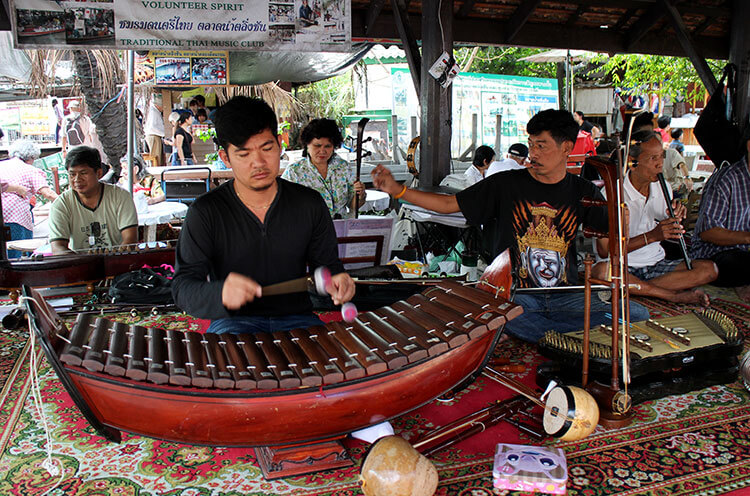 A volunteer Thai music club plays their instruments at the Taling Chan Floating Market