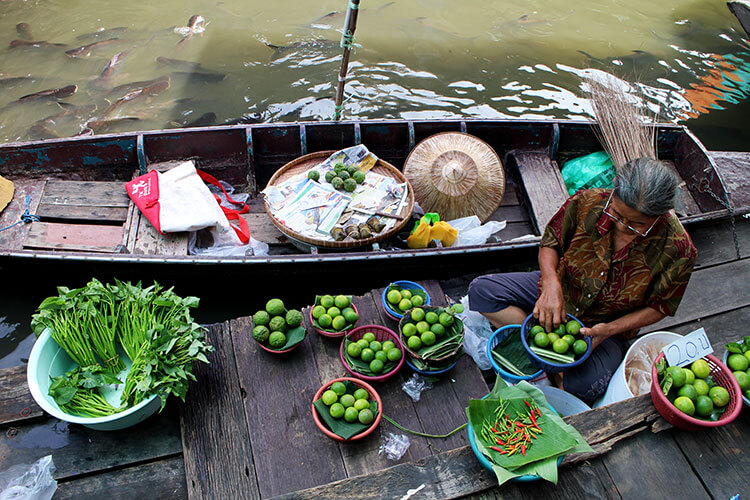 A woman sorts bowls of Thai limes in her boat at the Taling Chan Floating Market