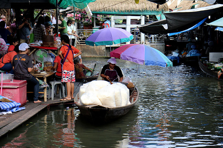 Five huge bags of rice fill a woman's boat and she cooks in a giant wok selling rice to the patrons on the riverside