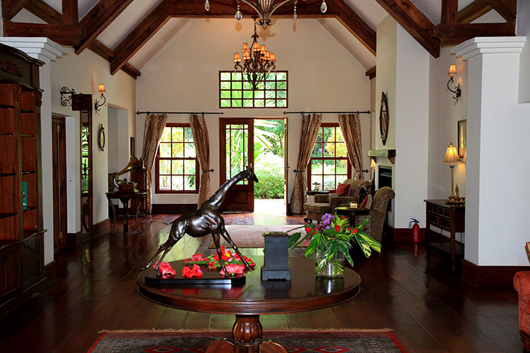 The main room in The Manor at Ngorongoro is decorated in dark woods, has a high ceiling with a chandelier and sitting areas for guests to relax