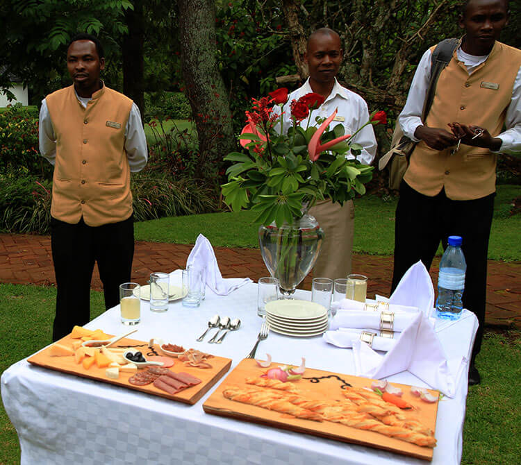 Three butlers wait with a table of snacks with cheese, bread and lemonade at The Manor at Ngorongoro