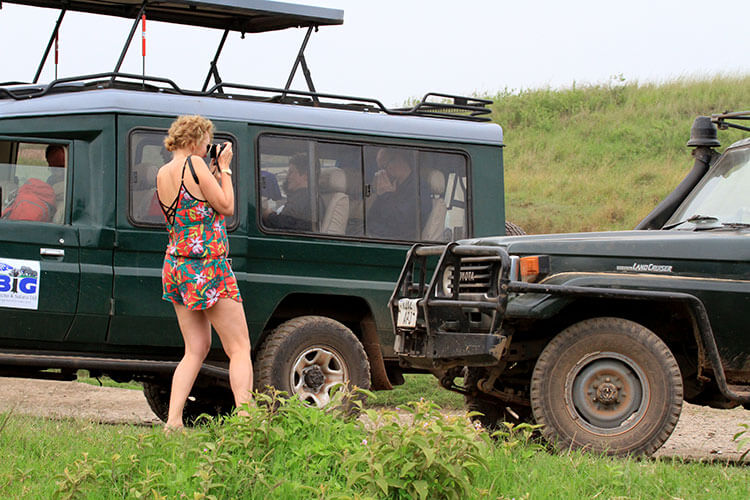 A woman in a bright floral short jumpsuit and flip flops demonstrates what not to wear on safari in Ngorongoro Crater, Tanzania