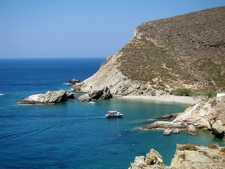 View from the cliff above Agios Nikolaos Beach with a small boat crossing to the beach