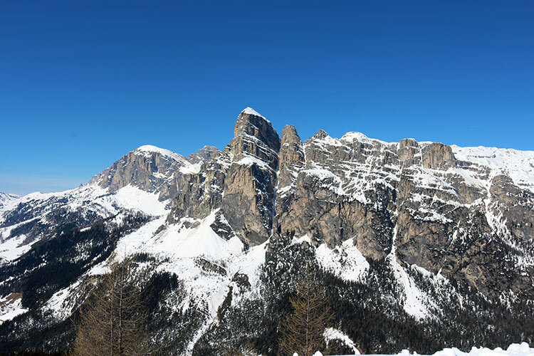 Val Scura's nearly 1000 meter drop is seen in the narrow crevice between the peaks from a viewpoint