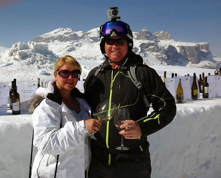 Me and Tim at Utia l Tabla on the Wine Ski Safari clinking our glasses with blue skies and smowy mountains behind us