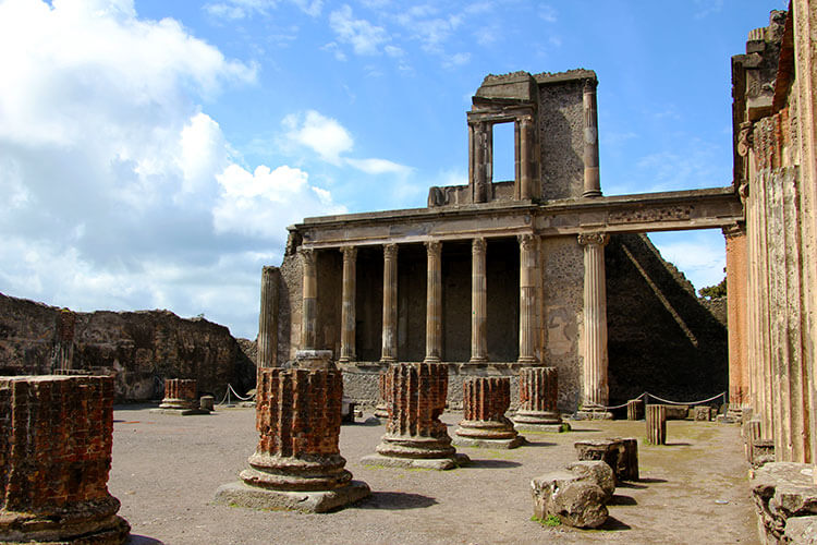 The ruins of four columns sit in front of the skeleton remains of the Basilica at Pompeii