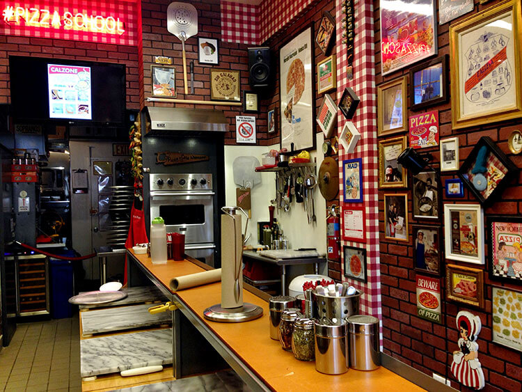 The interior of Pizza School NYC decorated with posters and memorabilia all over the kitchen walls