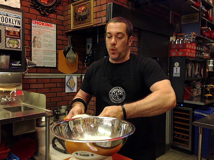 Mark measures some flour into a mixing bowl as he demonstrates how to make pizza dough at Pizza School NYC