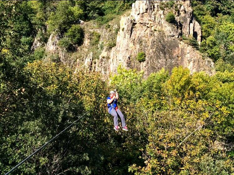 Jennifer on the zipline at the end of the first section of Via Ferrata du Pont du Diable
