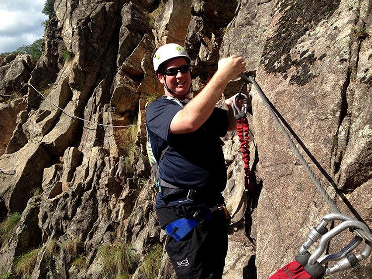 Tim navigating a section of rock wall on the Via Ferrata du Pont du Diable