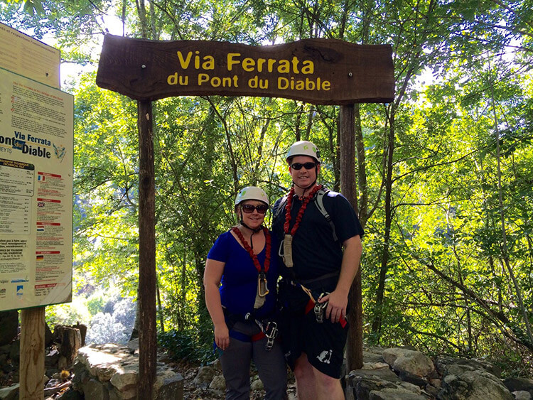 Jennifer and Tim wearing helmets and climbing gear at the entrance to Via Ferrata du Pont du Diable
