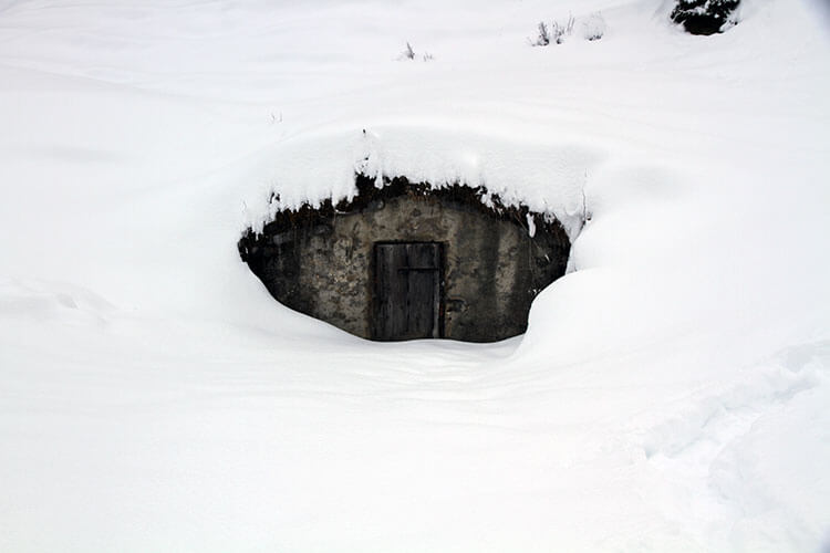 A Reblochon cheese cave almost completely covered by snow