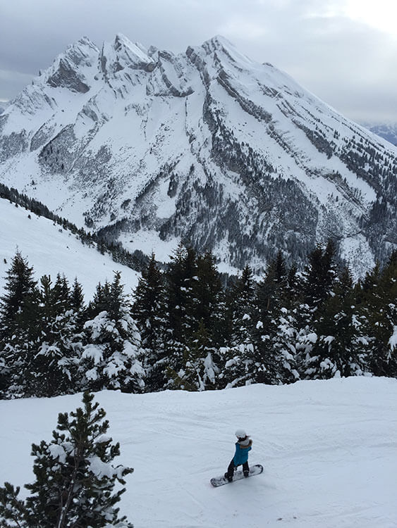 A snowboarder on a beginner piste at Le Grand Bornand
