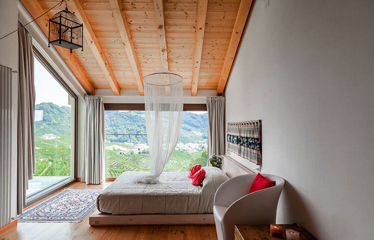 "A room at Agriturismo due Carpini with two floor to ceiling glass ""walls"" with vineyard views"