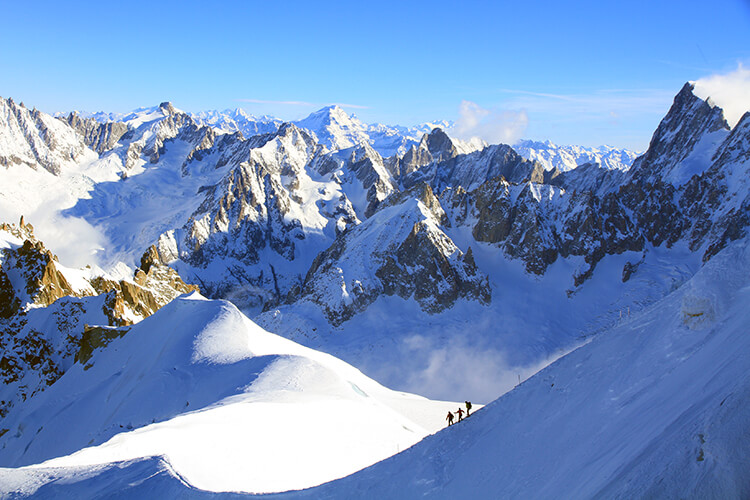 Off-piste skiers make their way down the ridge from Aiguille du Midi on Mont Blanc