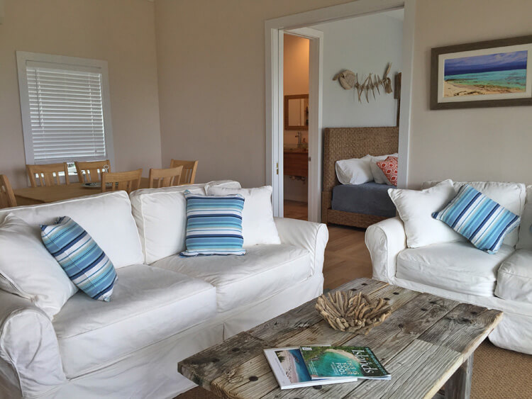 The living room of the Sandy Toes cottage is decorated with two overstuffed white couches with bright throw pillows, a wooden coffee table and photos on the walls of Rose Island, Bahamas