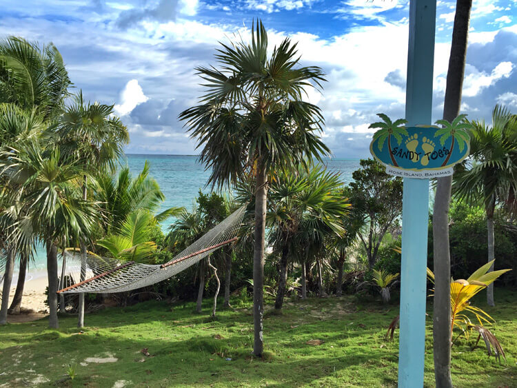 "A sign near the hammocks reads ""Sandy toes and salty kisses"" at Sandy Toes Rose Island, Bahamas"