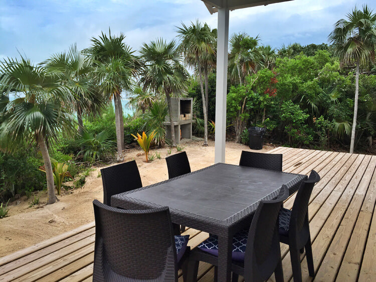 The outdoor deck with dining table and barbecue at the Sandy Toes cottage on Rose Island, Bahamas