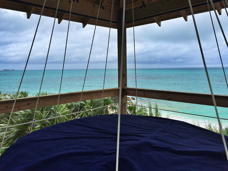 The view of the beach and sea from the treetop swing at the Sandy Toes cottage on Rose Island, Bahamas