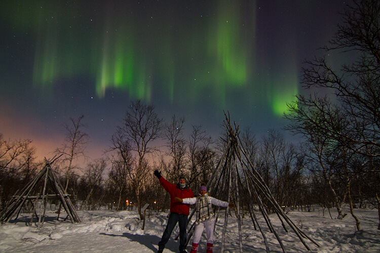Jennifer and Tim pose under a green and purple curtain of Northern Lights in Abisko, Sweden