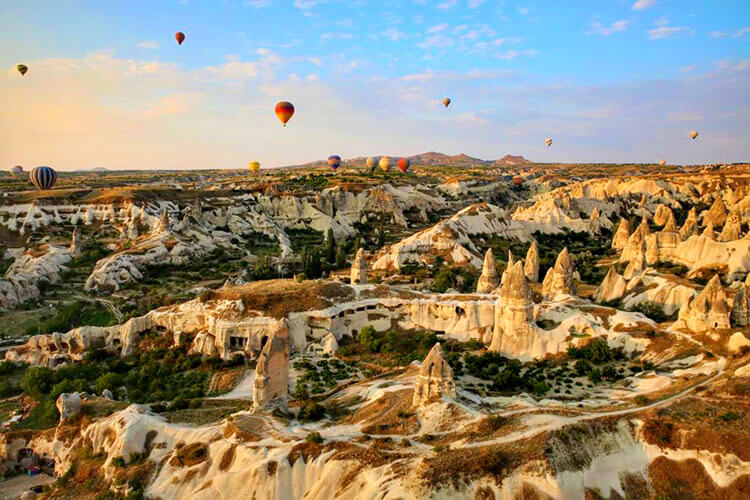 Sunrise at Cappadodica with fairy chimneys dotting the landscape and more than 100 hot air balloons in the sky