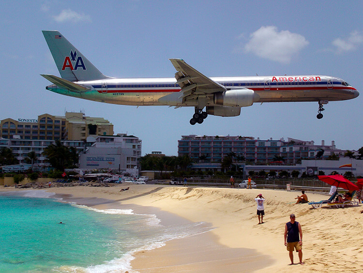 Plane landing in St. Maarten very low over some beach goers heads on Maho Beach just behind the St Maarten airport