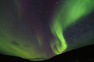 The Northern Lights appear like a candle flame shooting out of the mountain in Iceland's Westfjords